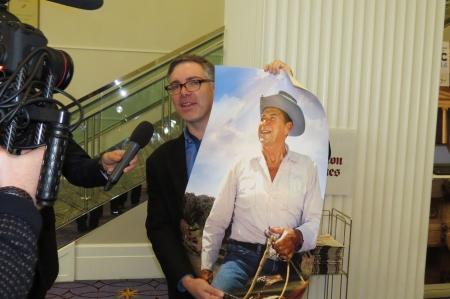 Matt Lewis holds up a Ronald Reagan poster
