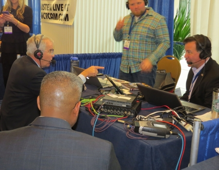 Oliver North talks to Lars Larson while Allen West waits in the wings on radio row.