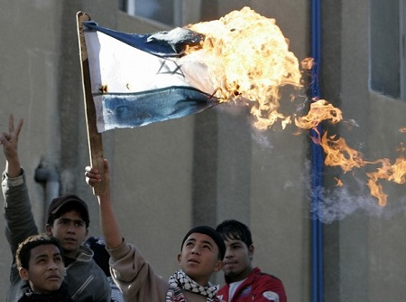 Palestinian protesters burn an Israeli flag during a demonstration at Palestinian refugees Camp Al-Baqaa near Amman