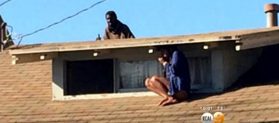 The Terrifying Story of This Photo of a Woman Crouched on Top of Her Roof