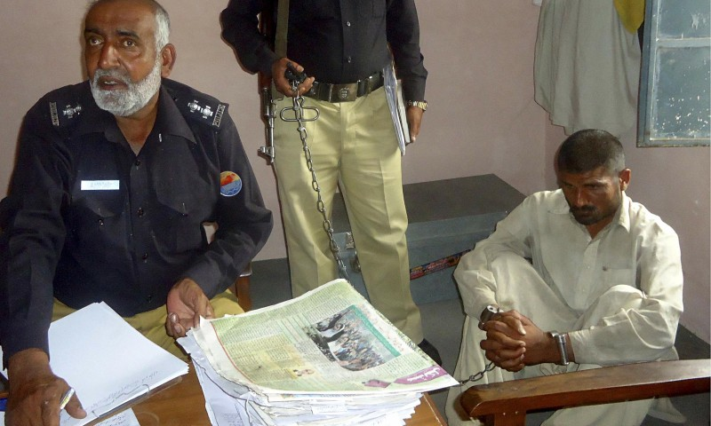 Mohammad Arif sits at a police station after his arrest