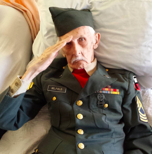 This Nov. 11, 2014 photo provided courtesy of Nancy McKiernan of Baptist Health Nursing and Rehabilitation Center in Glenville, N.Y., shows 98-year-old World War II veteran Justus Belfield saluting on Veterans Day
