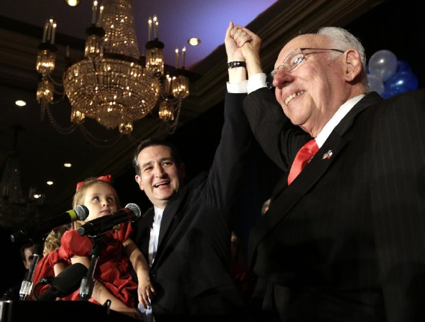 Republican presidential candidate Sen. Ted Cruz, left, raises his hand with his father Rafael, right, while holding his daughter Caroline during a speech Tuesday, Nov. 6, 2012, in Houston. (AP Photo/David J. Phillip)