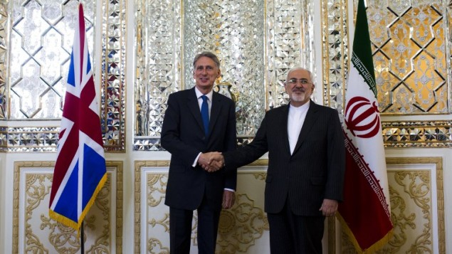 Iranian Foreign Minister Mohammad Javad Zarif (R) shakes hands with his British counterpart Philip Hammond prior to their joint press conference in Tehran on August 23, 2015. (AFP PHOTO/BEHROUZ MEHRI)