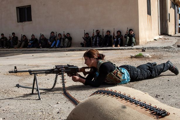 A-Syrian-Kurdish-young-woman-practices-for-shooting