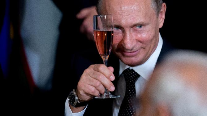 Russian President President Vladimir Putin holds up a glass during a toast at a luncheon hosted by United Nations Secretary-General Ban Ki-moon, Monday, Sept. 28, 2015, at United Nations headquarters. (AP Photo/Andrew Harnik)