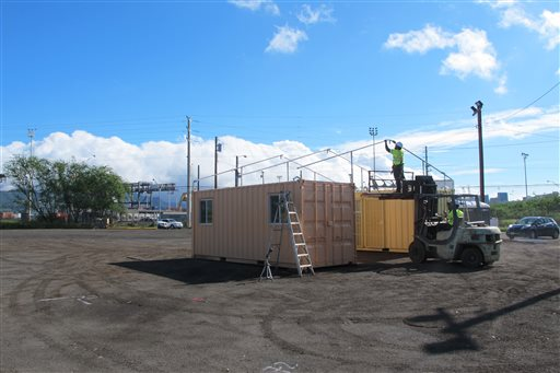 Crews work on an awning at the city's latest homeless shelter on Friday, Oct. 16, 2015 in Honolulu. The housing units are made from converted shipping containers and will be located on Sand Island, and industrial part of Honolulu. (AP Photo/Cathy Bussewitz)