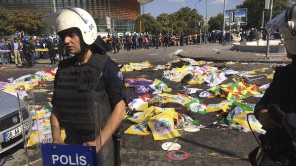 Oct. 10, 2015: Bodies of victims are covered with flags and banners as a police officer secure the area after an explosion in Ankara, Turkey. (AP)