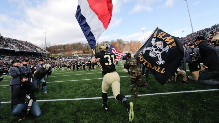 Army's Caleb McNeill carries the French flag onto the field Saturday at Michie Stadium. Mike Groll / Associated Press