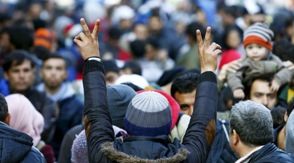 Migrants gesture after arriving at the Austrian-German border in Achleiten near Passau, Germany, October 27, 2015. Michaela Rehle / Reuters