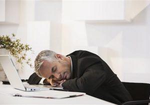 Businessman sleeping at desk in office (Blend Images via AP Images)