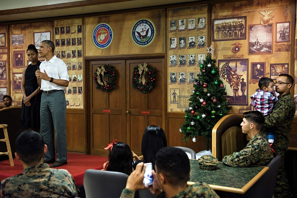 US first lady Michelle Obama (L) listens while US President Barack Obama speaks to members of the US Marines, their loved ones and others to celebrate the holidays during Christmas Day at Marine Corps Base Hawaii December 25, 2015 in Kaneohe Bay, Hawaii. Obama and the First Family are in Hawaii for vacation. AFP PHOTO/ BRENDAN SMIALOWSKI / AFP / BRENDAN SMIALOWSKI (Photo credit should read BRENDAN SMIALOWSKI/AFP/Getty Images)