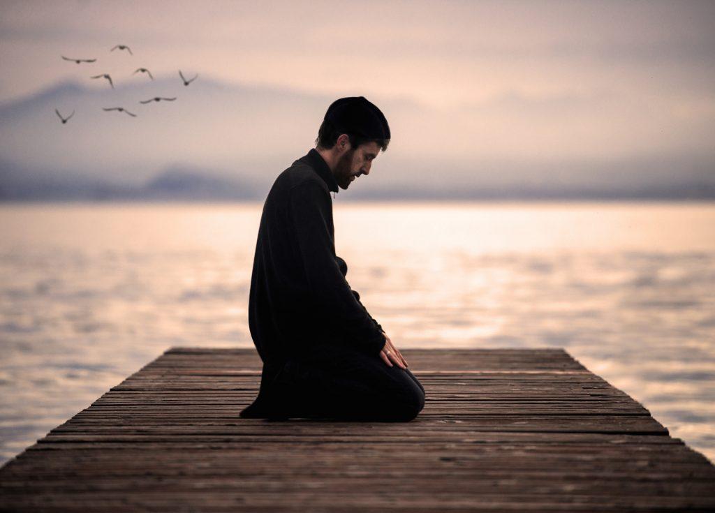 Muslim man praying on an empty dock