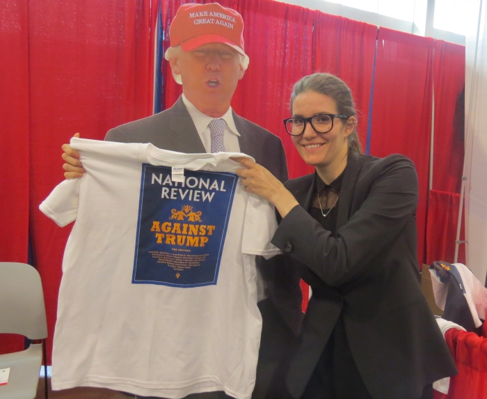 "Inez Feltscher holds up NR's ""Against Trump"" t-shirt at the National Review booth"