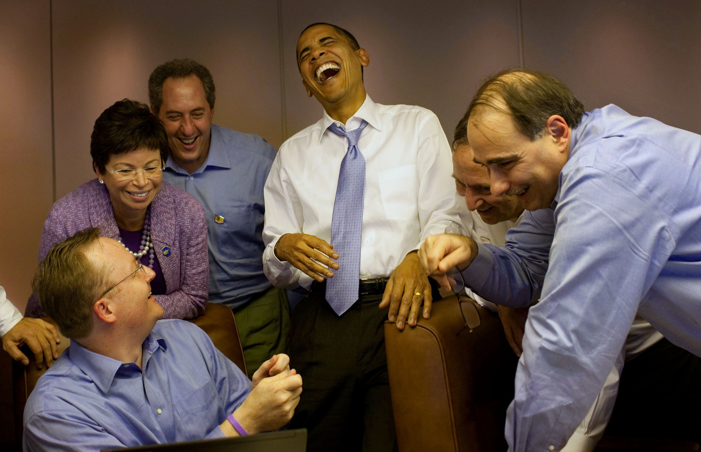 President Barack Obama laughs with aides aboard Air Force One en route to Singapore, Nov. 14, 2009.