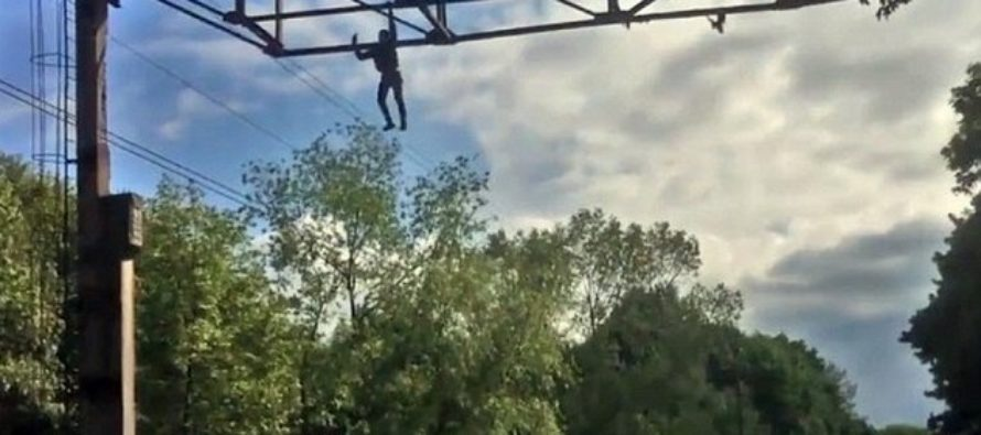 VIDEO: Daredevil Takes a Selfie Hanging From One Hand Above a Railway… Then Falls to the Ground