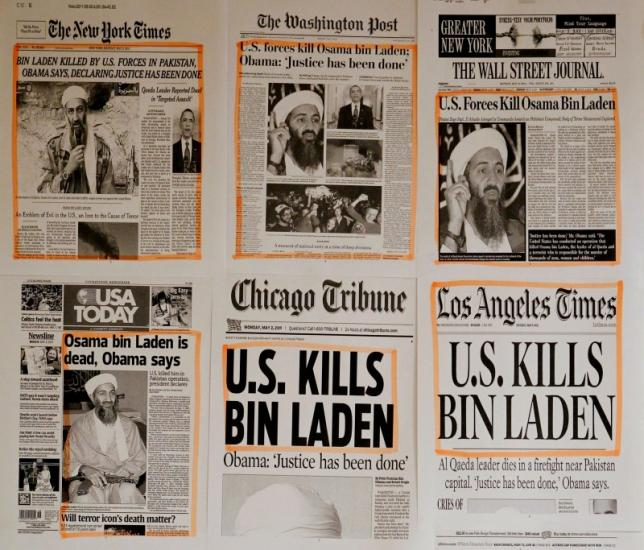 Newspaper headlines and clippings are posted on a wall inside a staff office at the White House in Washington