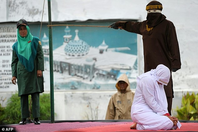 38axontzl34fffffd23ae53e11ce-3843916-a_muslim_woman_is_caned_in_banda_aceh_indonesia_on_october_17_20-a-10_1476709281382