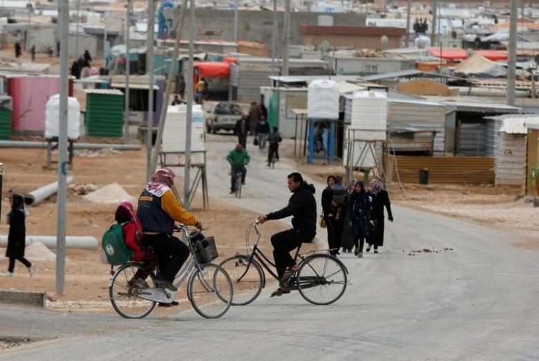 Syrian refugees ride bicycles on the main street of Al Zaatari refugee camp in Jordan, near the border with Syria, November 30, 2016. REUTERS/Muhammad Hamed
