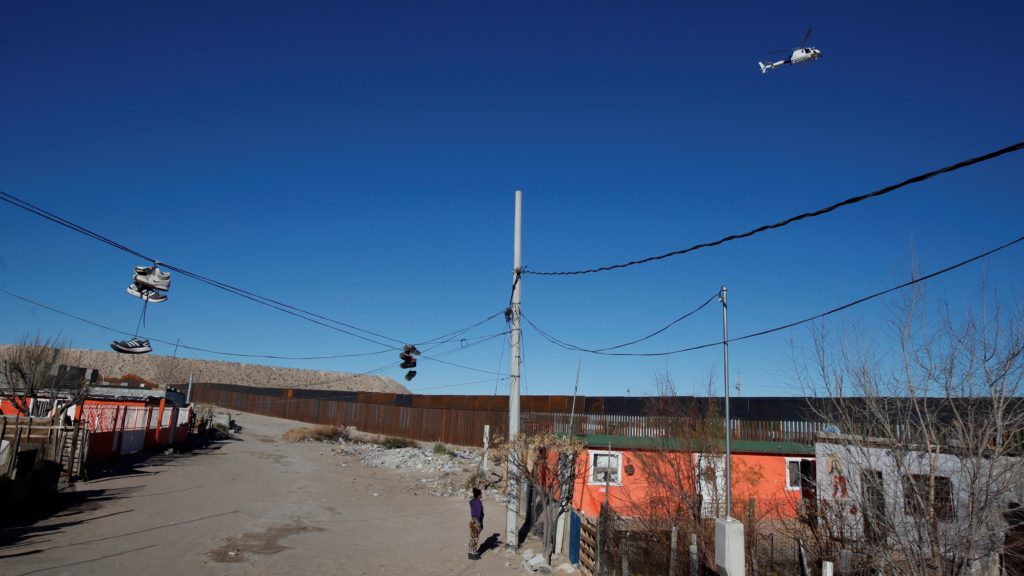 A woman stands outside her house as a Border Patrol helicopter flies over a newly built section of the U.S.-Mexico border fence at Anapra neighbourhood in Ciudad Juarez